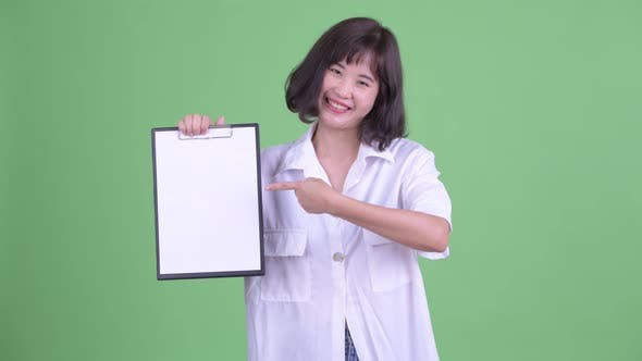 Thumbnail for Happy Asian Businesswoman Showing Clipboard and Giving Thumbs Up