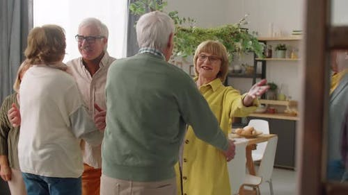 Cheerful Senior Couple Greeting Friends at Home