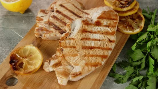Roast Turkey Fillet with Slices of Lemon on Cutting Board.