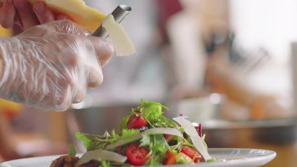 Hands of Chef Grating Cheese on Salad