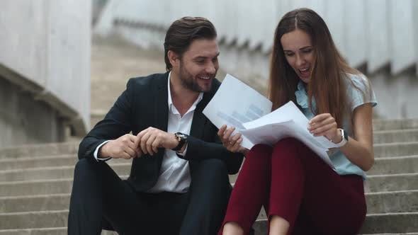 Thumbnail for Businesswoman and Businessman Looking at Hight Graphs on Papers at Street