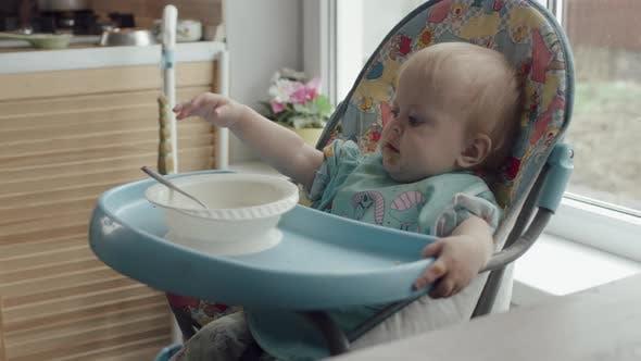 Kleines Kind isst sich selbst Löffel Babynahrung im Babystuhl zu Hause
