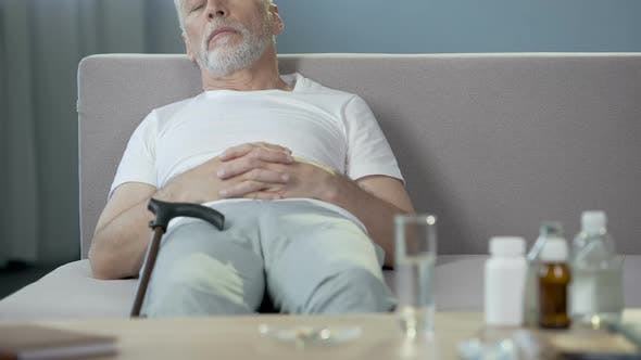 Ill Lonely Grandfather Sleeping on Sofa, Medicaments Standing on The Table