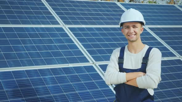 Cover Image for Portrait of a Young Worker in a White Helmet on the Background of Solar Panels