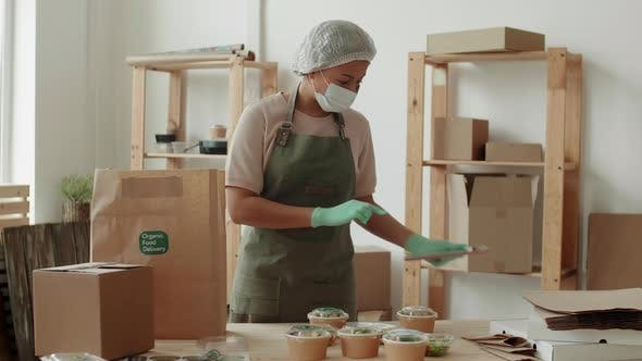 Female Employee Collecting Food Boxes for Delivery