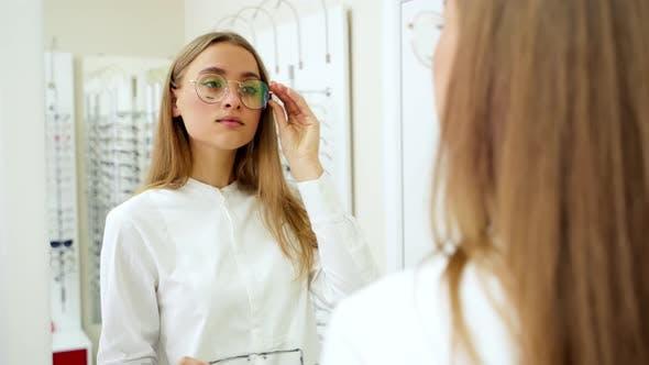Thumbnail for Beautiful girl wearing eyeglasses. Elegant fasionable woman choosing eyeglasses in optical store