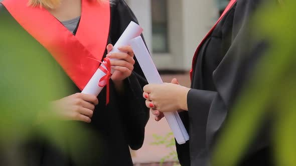 Thumbnail for Female Students Holding Diplomas and Chatting in Park, Higher Education
