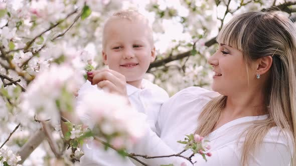 Mother and Little Son Standing Near Flowering Tree in Village