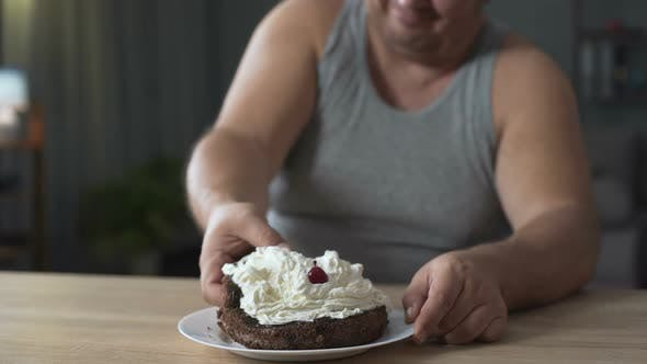 Cover Image for Obese Person Eating Cake with Whipped Cream Greedily and Quickly, Addiction