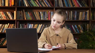Concentrated Schoolgirl Looks at Laptop Screen and Writes