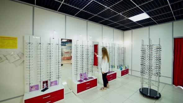 Thumbnail for Woman at optical shop. Woman choosing her new glasses at optics store