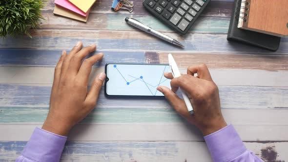 Young Man Analyzing Stock Chart on Smart Phone