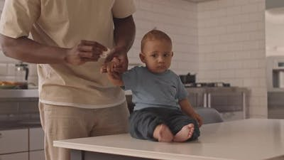 Parent Cleaning Hand of Baby on Table