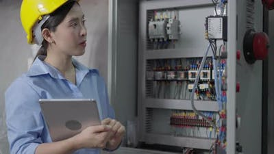 Female engineer checking on electric system in construction site