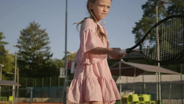 Thumbnail for Adorable Funny Girl with Two Pigtails Playing Tennis Outdoors