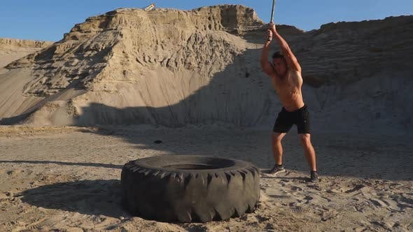 Cover Image for Muscle Athlete Strongman Man Hits a Hammer on a Huge Wheel in the Sandy Mountains in Slow Motion