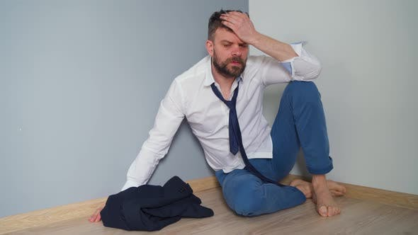 Thumbnail for Upset Bearded Man in Untidy Formal Clothes Is Sitting Lies on the Floor in an Empty Apartment. The