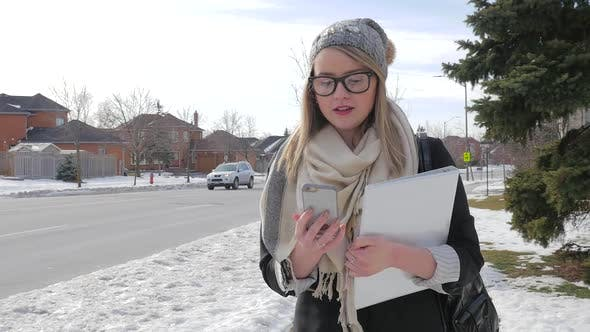 Thumbnail for A Young Female Walking Outside Wearing A Scarf And Hat Looking At Her Smart Phone