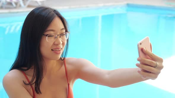 Close Up Happy Asian Ethnicity Woman in Glasses Making Selfie Portrait Photo on Camera Phone Gadget