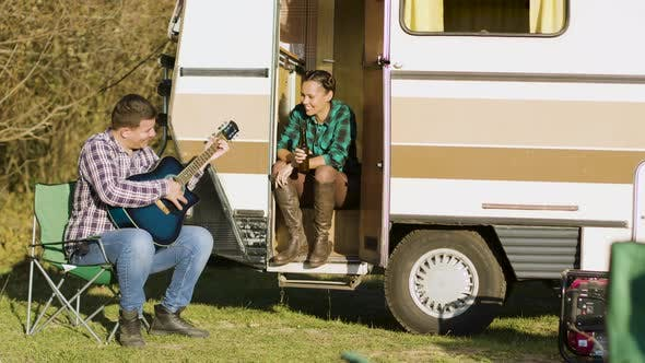 Thumbnail for Boyfriend in Front of the Retro Camper Van Singing on Guitar
