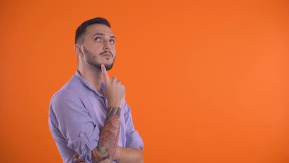 Thumbnail for Thoughtful Man Thinking with Finger on Face, Isolated on Orange Background.