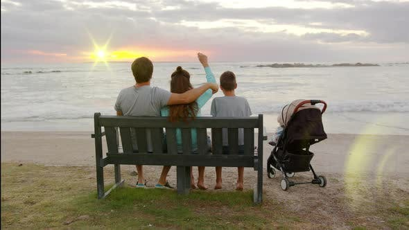 Happy Family Siting on the Bench at Sunset By the Ocean