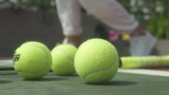 Tennis Balls and Racket on the Court Ground with a View of Woman