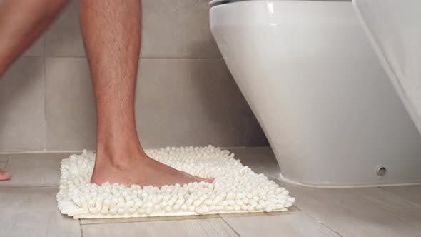 Man Sitting on Wc Toilet Bowl at the Bathroom and Holding a Toilet Paper Roll