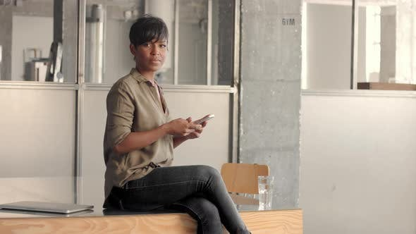 Young Mixed Race Black Woman Sits Above the Table and Text in Smartphone