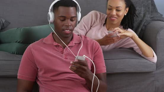 Thumbnail for African American couple listening to music and taking picture with smart phones