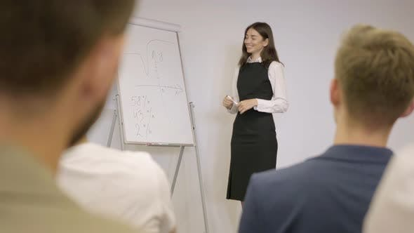 Cute Businesswoman Presenting New Project To Partners with Flip Chart