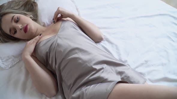 Thumbnail for Cute Girl in Short Nightwear with Bright Makeup Lying on the Bed
