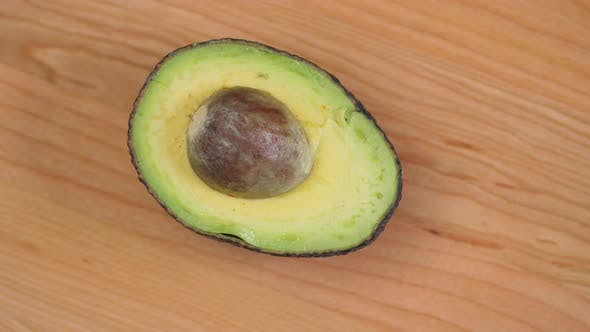 Cover Image for Half An Avocado With Nut Spinnin On Cutting Board 02