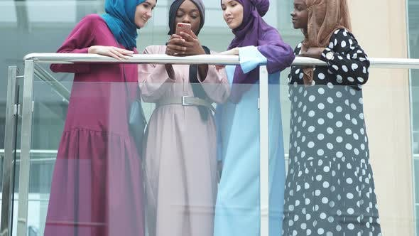 Thumbnail for Muslim Multiethnic Group of Girls Looks at Smart Phone in Hand of African Woman