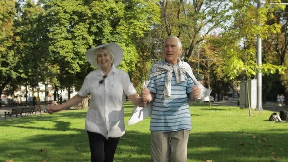 Thumbnail for Senior Happy Two Tourists Running and Bouncing in Town Center Park