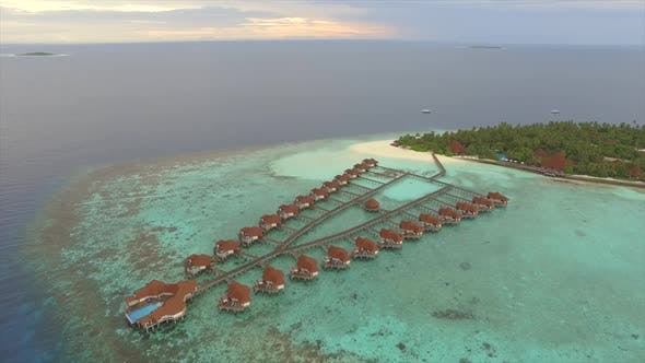 Aerial view of overwaters bungalows connected by a footbridge, Maldives.