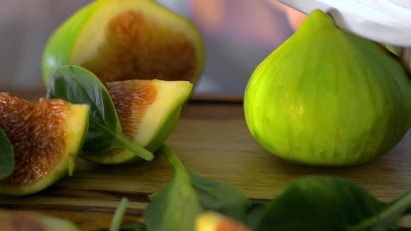 Cover Image for Cut Green Figs and Basil Leaves