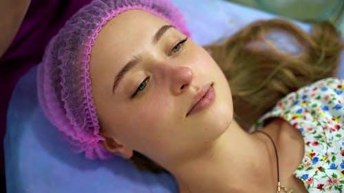 Esthéticienne professionnelle effectue des procédures faciales sur le visage de la fille.