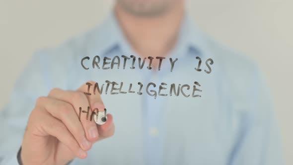 Creativity is Intelligence Having Fun, Man Writing on Transparent Screen