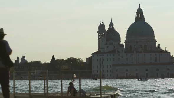 Thumbnail for People chilling on pier, hit by choppy waters of river with cathedral across it