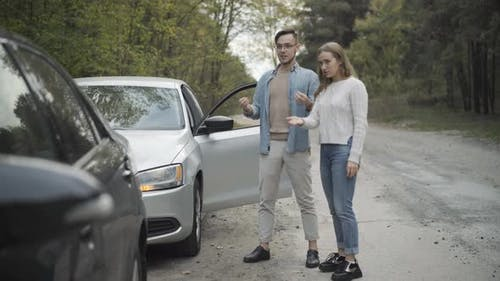Wide Shot of Young Caucasian Man and Woman Talking and Gesturing Looking at Broken Cars on Roadside