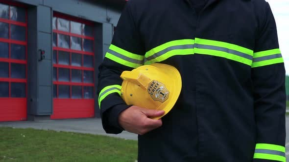 Thumbnail for A Firefighter Stands in Front of a Fire Station with His Helmet on His Side - Closeup