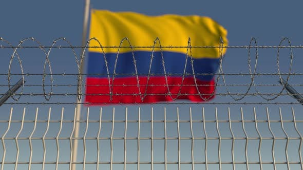 Cover Image for Blurred Waving Flag of Colombia Behind Barbed Wire
