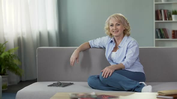 Thumbnail for Gorgeous Mature Female Sitting on Couch and Looking Into Camera, Advertisement