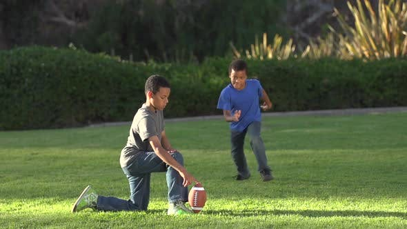 Thumbnail for Two brothers kicking a football