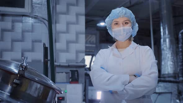 Female Worker in Medical Mask Stands Near Machine Tool