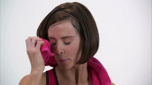 Royalty Free Stock Footage of Close up of a woman patting herself dry after a workout and smiling.