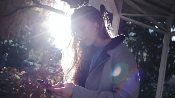 Thumbnail for Sunlit Woman Looking At Smartphone