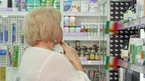 Thumbnail for Elderly Female Customer Examining Medical Products for Sale at the Drugstore