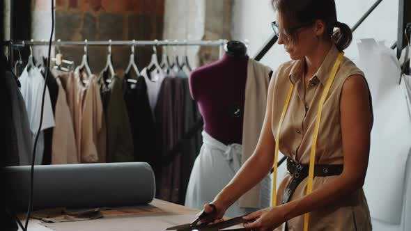 Thumbnail for Female Dressmaker Cutting Fabric with Scissors in Sewing Studio